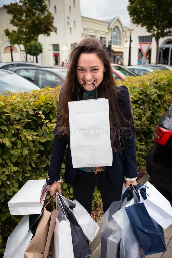 Young happy woman holds many shopping bags in tooth and hands royalty free stock image