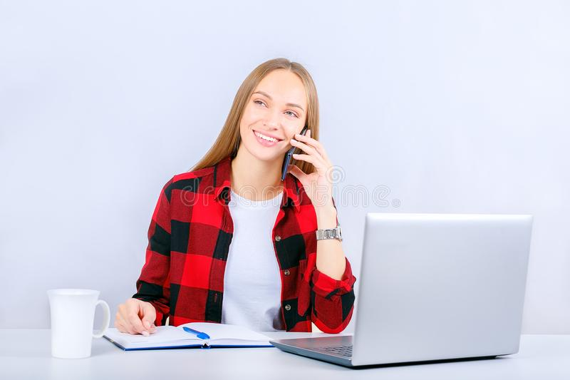 Young happy woman at home or office using laptop computer talking by mobile phone. royalty free stock image