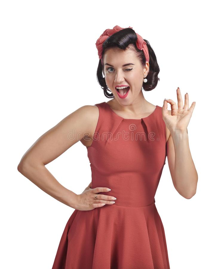 Free Young Happy Woman In A Coral Dress Showing Okay Sign,  Looking Into The Camera, Eye Narrowing Royalty Free Stock Photography - 166678237