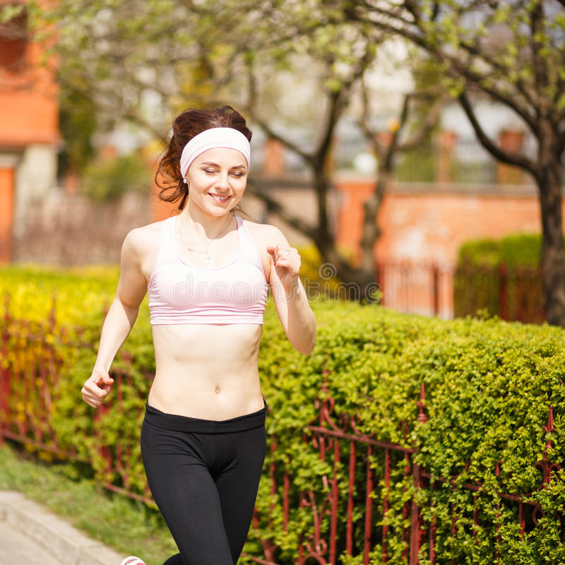 Young happy woman jogging along the street stock photos