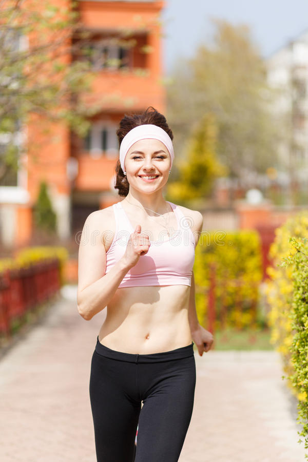 Young happy woman jogging in the street royalty free stock images