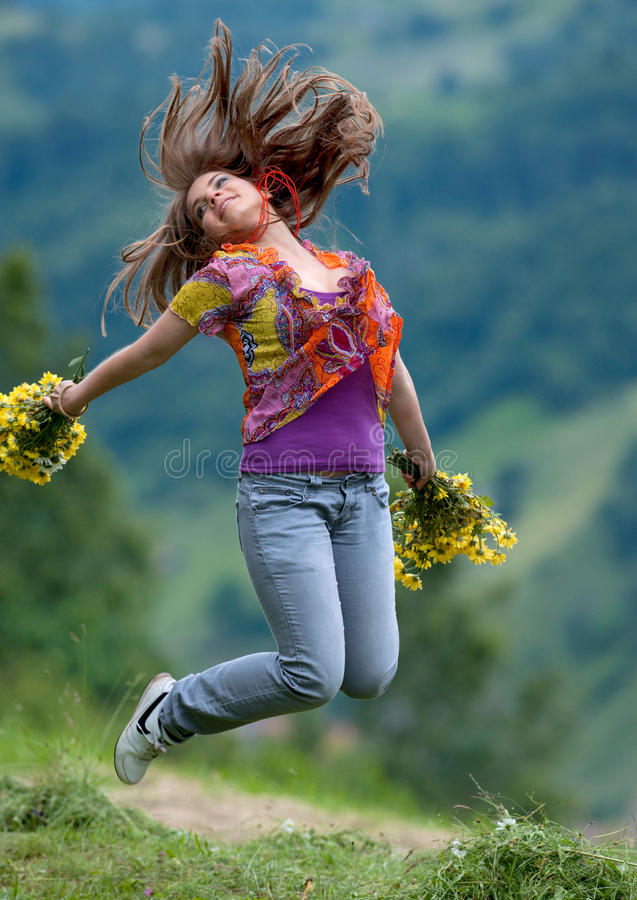 Young happy woman jumping. On the field in summer stock photo