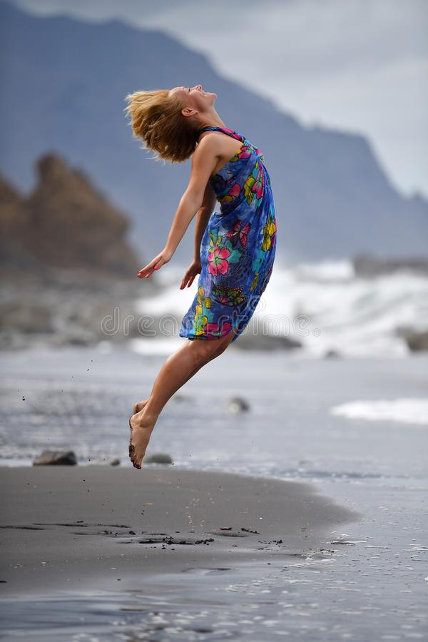 Young woman jumping on the beach in summer evening stock photos