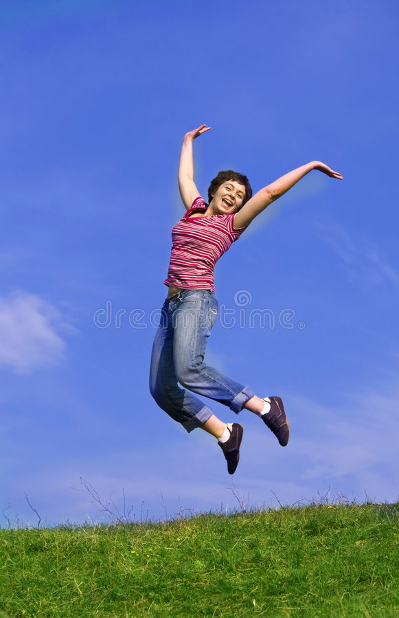 Young happy woman jumping high. Against blue sky royalty free stock photo