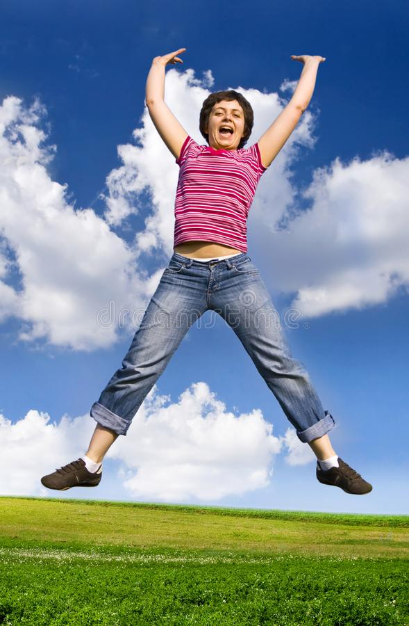 Young happy woman jumping high against blue sky stock photography