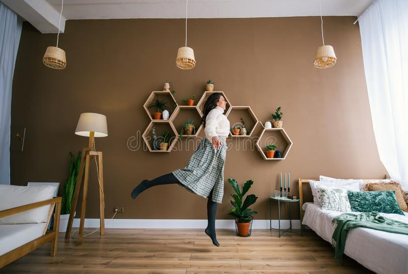 Young happy woman jumping up in living room with large sunny window in apartment stock image