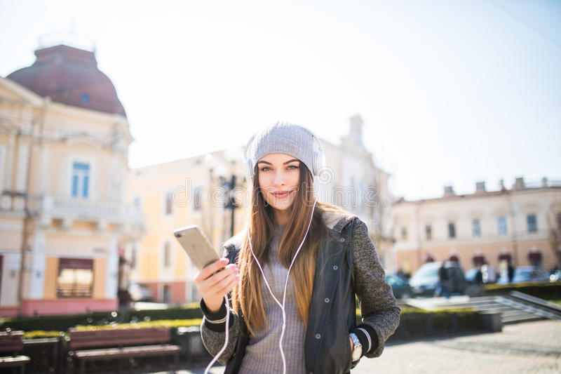 Young happy woman, listening music and having fun on the street Outdoor. stock images