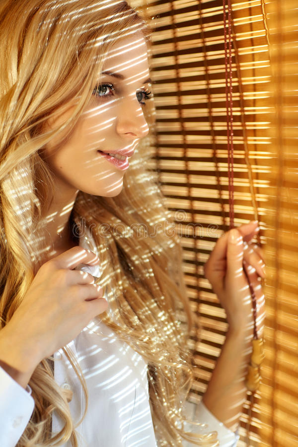 Young happy woman looking out the window through the blinds. Young blonde beautiful happy woman looking out the window through the bamboo blinds with Sun stock photo