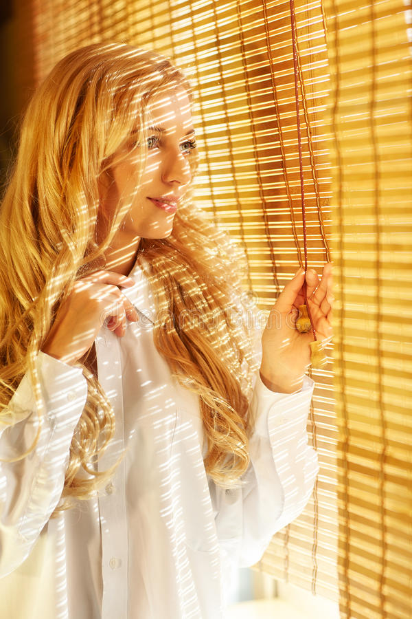Young happy woman looking out the window through the blinds. Young blonde beautiful happy woman looking out the window through the bamboo blinds with Sun stock image
