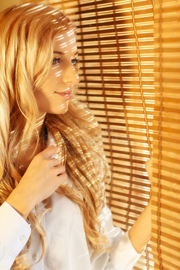 Young happy woman looking out the window through the blinds. Young blonde beautiful happy woman looking out the window through the bamboo blinds with Sun royalty free stock image