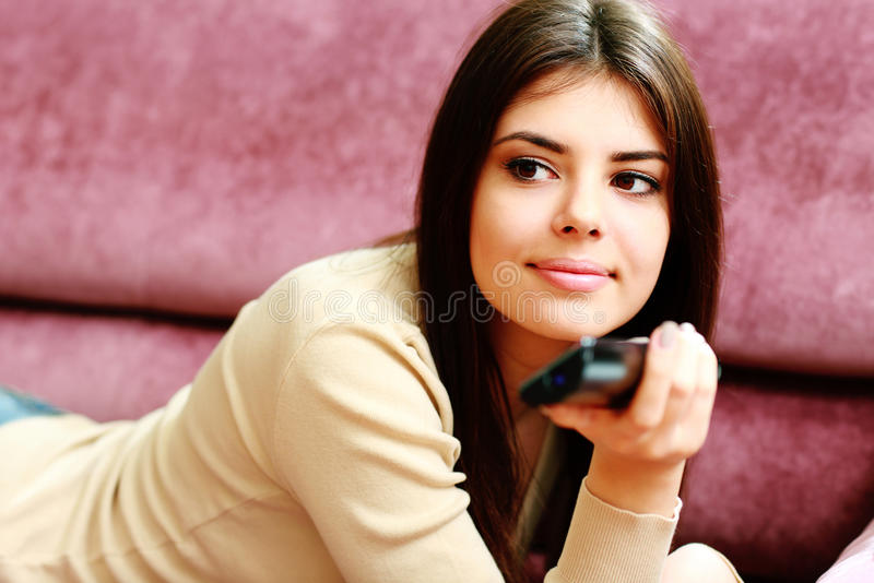 Young Happy Woman Lying On The Sofa With Remote Control Stock Image