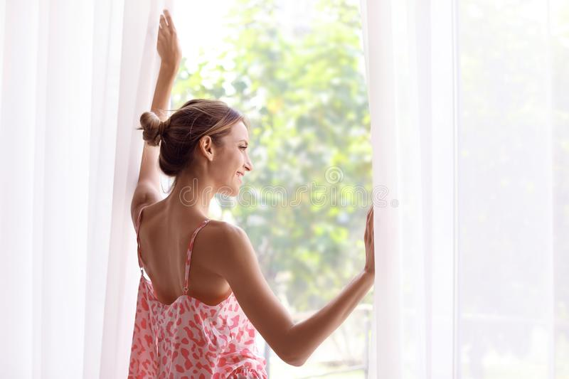 Young happy woman near window at home stock photos