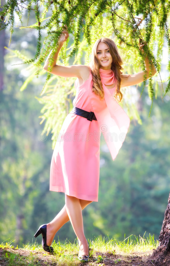 Young happy woman in pink dress. In a park stock photo