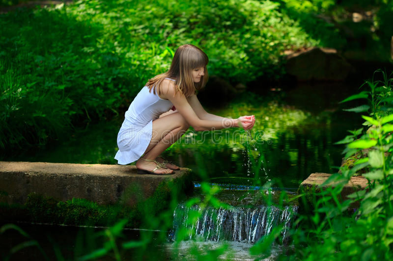 Young happy woman playing with water in the park royalty free stock image