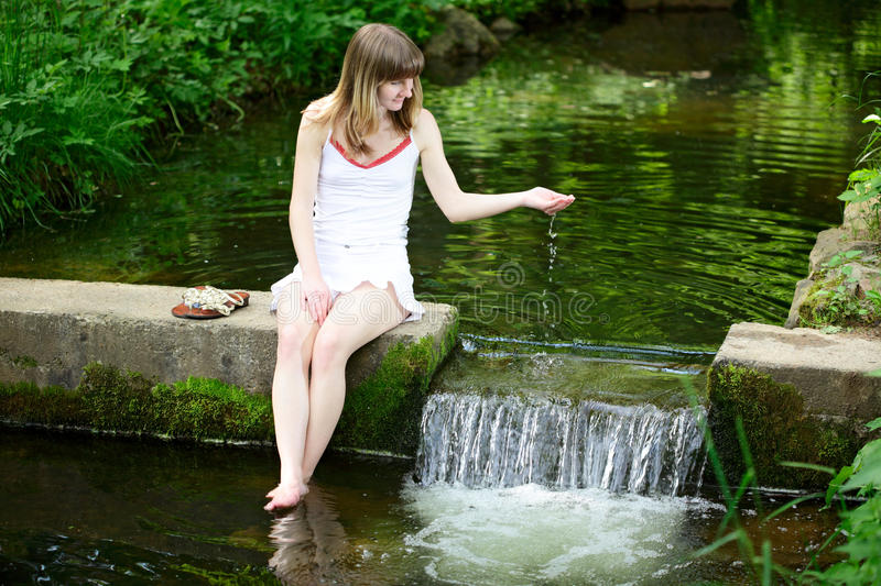Young happy woman playing with water in the park stock photos