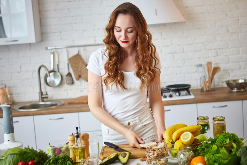 Young happy woman preparing tasty salad in the beautiful kitchen with green fresh ingredients indoors. Healthy food and Dieting stock image
