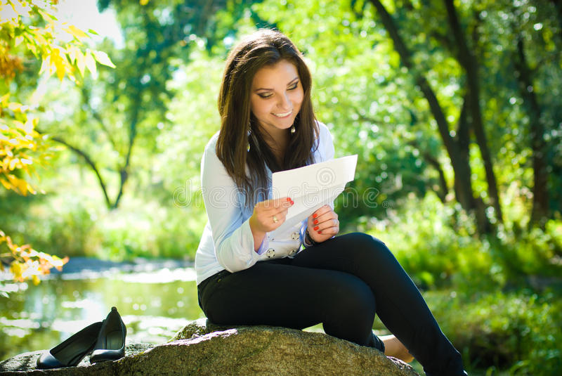 Young happy woman reading letter stock photo