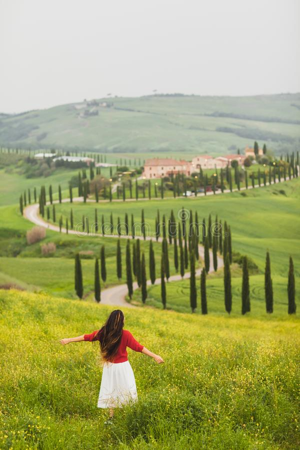 Woman in red sweater on spring Tuscany landscape. Young happy woman in red sweater and white skirt on background on spring Tuscany landscape. Dancing and royalty free stock photo