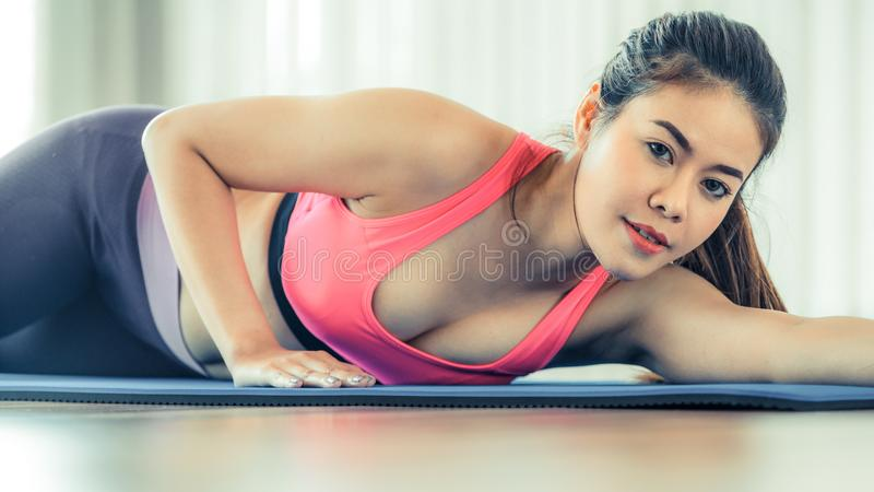 Young happy woman relaxing on yoga mat in gym royalty free stock images