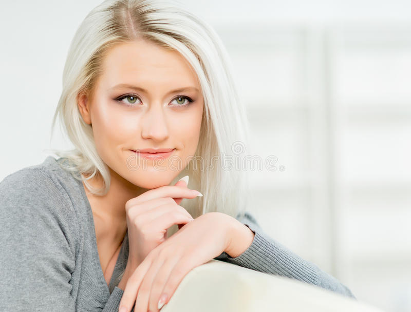 Young and happy woman resting on sofa at home.  stock photo