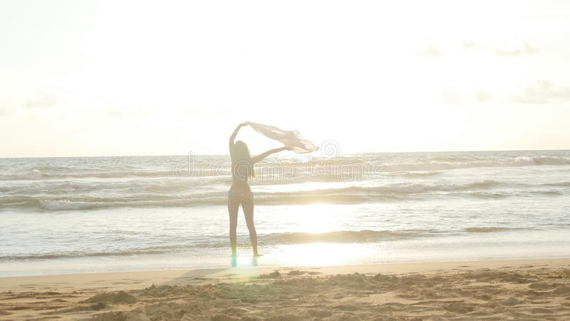 Young happy woman with scarf running on the ocean beach at sunset. Girl enjoying summer. Female in bikini with flying stock photo