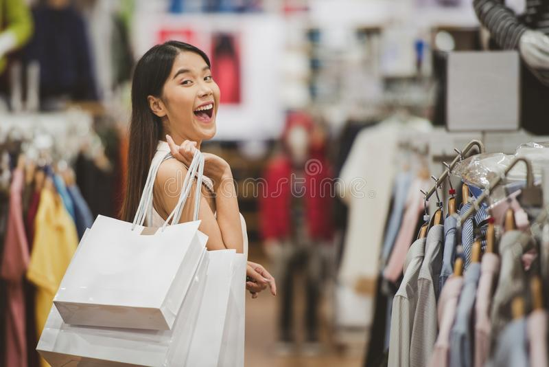 young happy woman with shopping bags in the luxury clothing store. royalty free stock photography