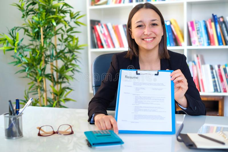 Young happy woman showing curriculum resume stock photography