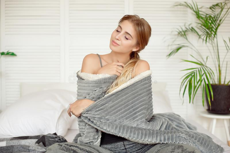 Young happy woman sitting on the bed in the morning wrapped up in white blanket in warm atmosphere.  royalty free stock images