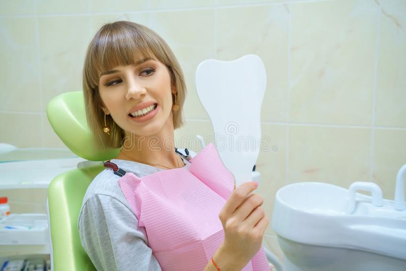 Young happy woman sitting in the dentist`s office, healthy teeth.  royalty free stock images