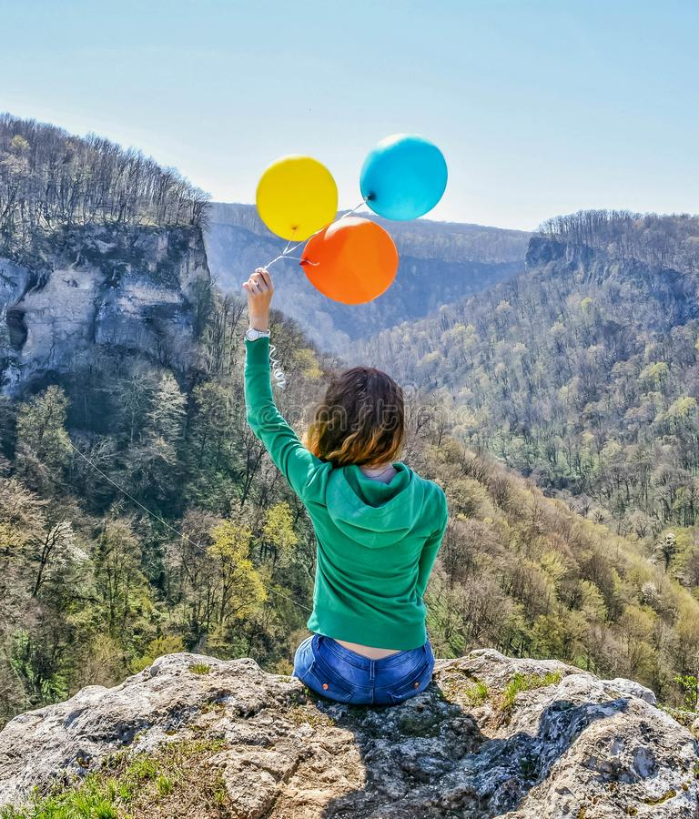 Young happy woman sitting on the edge of the cliff holding colorful balloons in her hands stock photo