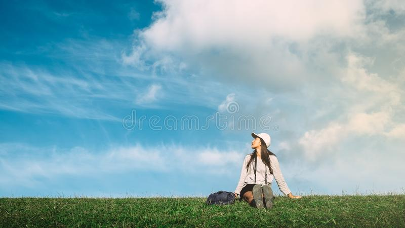 Young happy woman sitting on a green meadow. With blue cloudy sky on the background royalty free stock photo