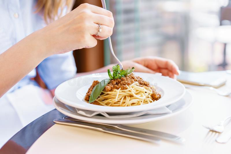 Young happy woman sitting at the table in cafe and enjoying the meal. Hungry woman eating tasty pasta. Dish of spaghetti stock photos