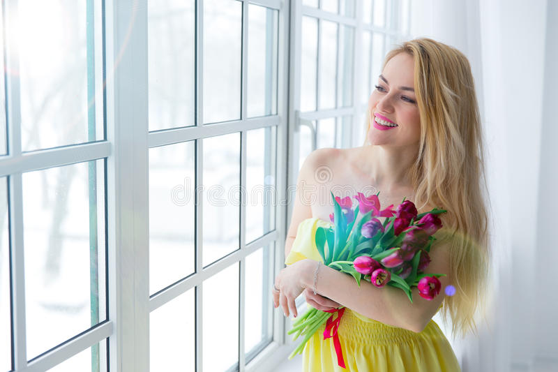 Young happy woman smiling with tulip bunch in yellow dress. 8 march international womens day. stock images