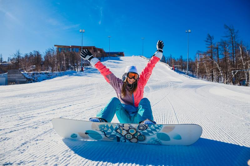 Young happy woman snowboarder sits on on a snowy mountain slope royalty free stock photography
