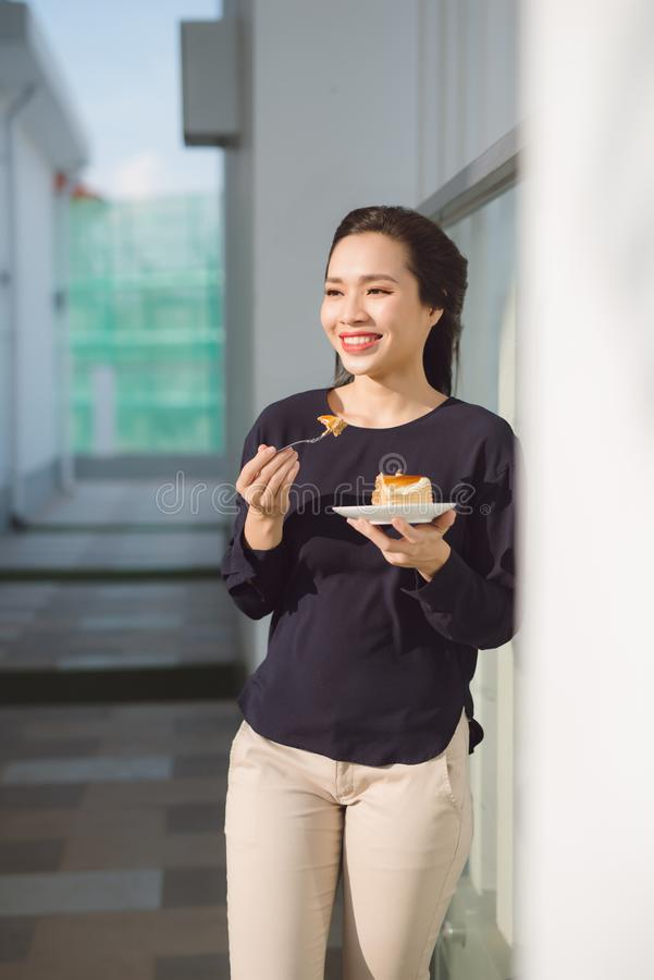Young happy woman stands on the terrace of the hotel with dish cake in the morning. Pretty asian girl in good mood and is ready stock photo