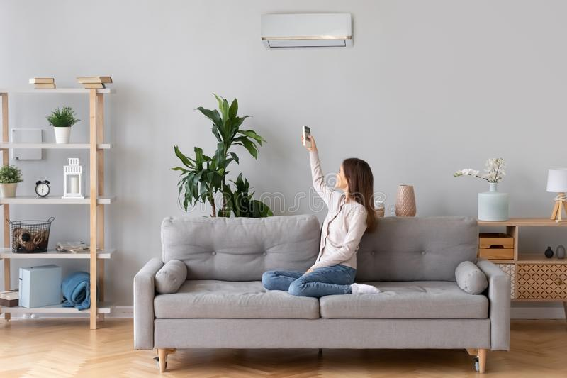 Young woman switching on air conditioner sitting on couch. Young happy woman switching on air conditioner sitting on couch at convenient cozy home, lady relaxing royalty free stock image