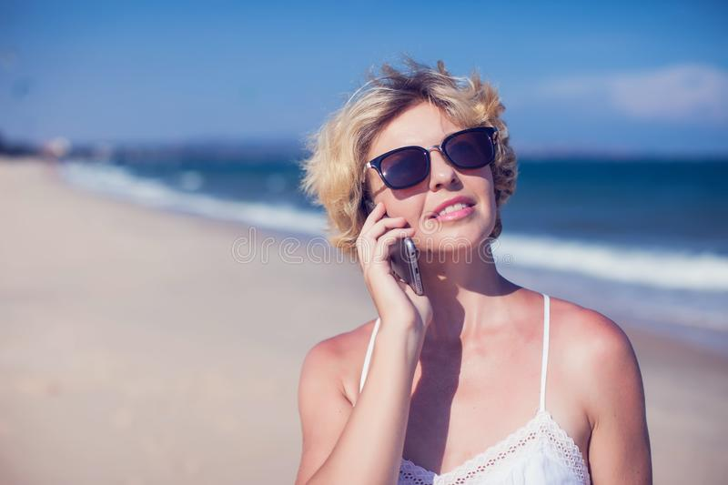 Young happy woman talking on mobile phone on a beach with sea ba royalty free stock photography