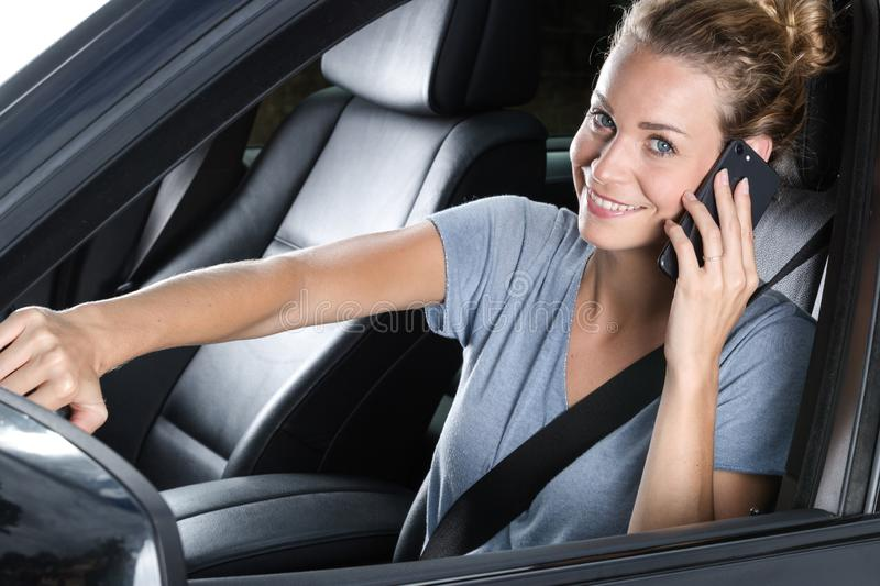 Young happy woman talking on phone in car stock image