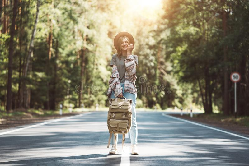 Young happy woman with traveling backpack wearing hat stand alone on countryroad stock image