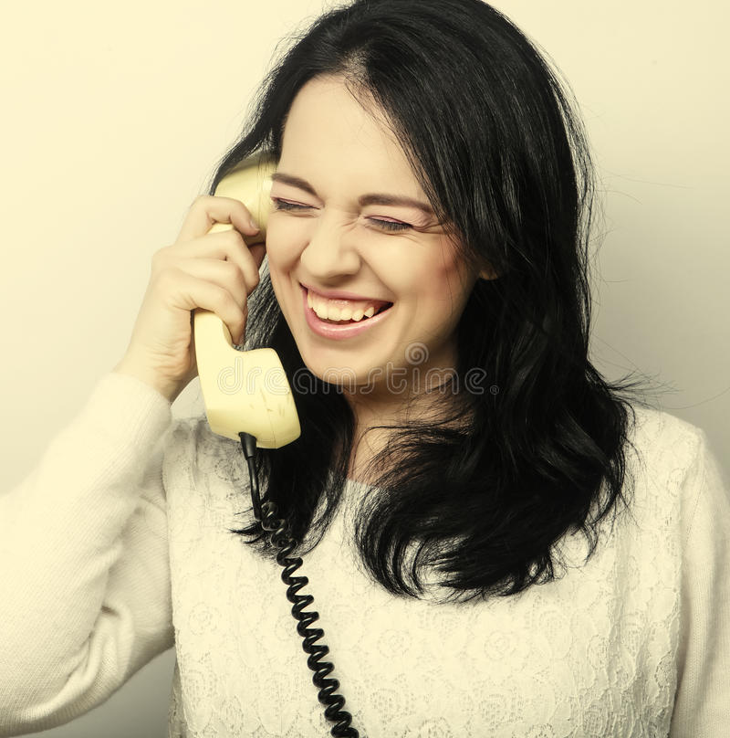 Young happy woman with vintage phone. Studio shot stock photography
