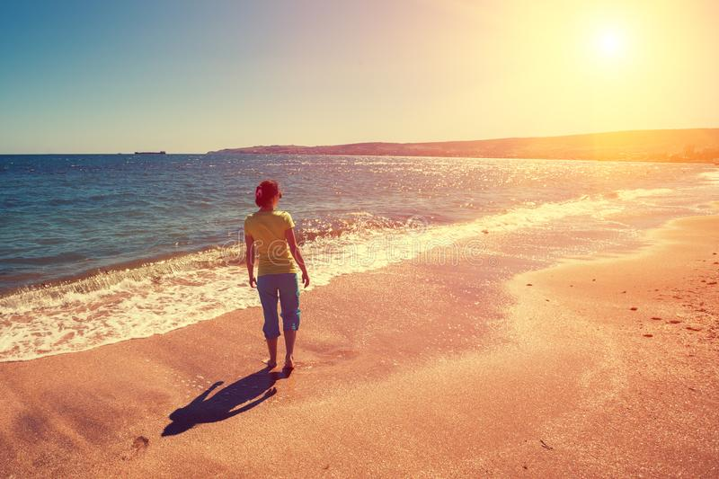 Young woman walking barefoot on the beach royalty free stock image