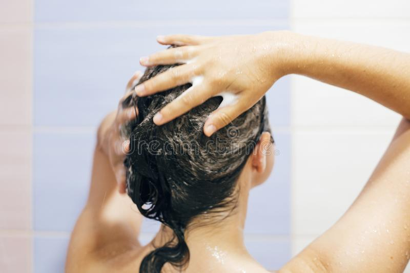 Young happy woman washing her hair with shampoo, hands with foam closeup. Back of beautiful brunette girl taking shower and stock photography