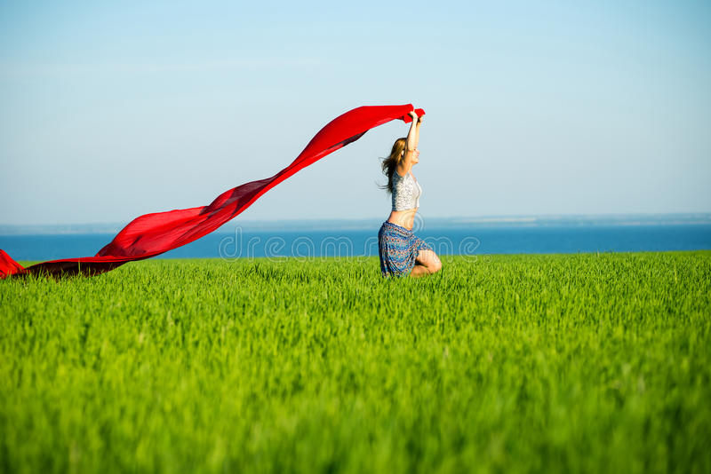 Young happy woman in wheat field with fabric. Summer lifestyle stock image