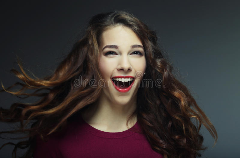 Young happy woman with wind in hair. Studio shot royalty free stock images