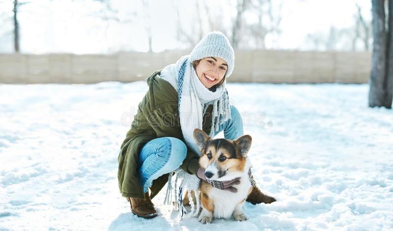 Young happy woman in woolen hat and long warm scarf smiling to camera and stroking her pet in snowy winter park at. Young happy woman in woolen hat and long warm royalty free stock photos