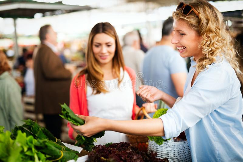 Young women friends baying vegetables and fruits on the market stock images