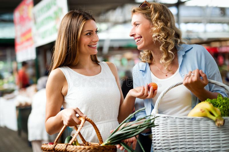 Young women friends baying vegetables and fruits on the market stock photos