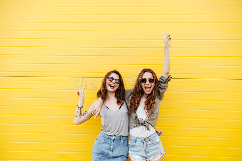 Young happy women friends standing over yellow wall royalty free stock photos