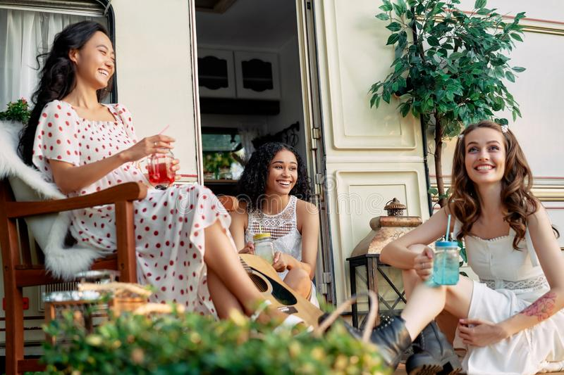 Young happy women have fun together enjoy picnic near their camper van during summer travel royalty free stock photo