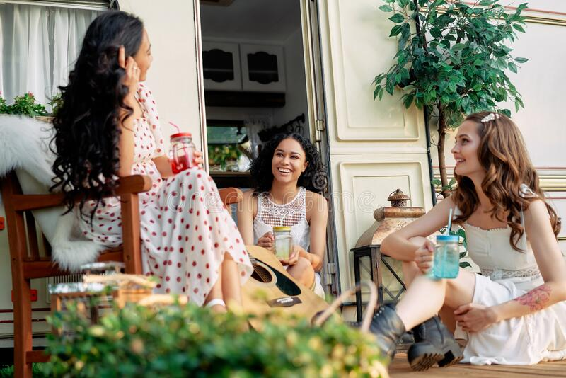 Young happy women have fun together enjoy picnic near their camper van during summer travel stock images